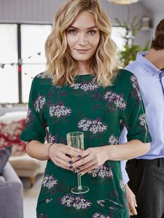 A gem of a tunic this loose fitting piece in an easy-breezy fabric features a floral print with textured flocking a folded round collar front pockets and a concealed back zip. You'll be layering tucking and belting this piece all year round.