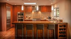 This Berkeley Mills Designed and Built, this Mozambique flat panel kitchen for young couples new Mid Century home in the hills above El Cerrito CA. The Faces are  Mozambique book matched veneers over Maple cabinets, The Bar top is laminated full length boards of Mozambique.