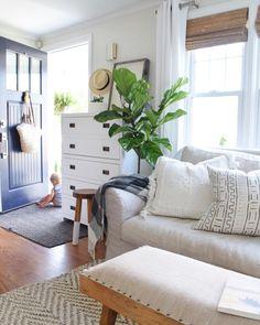 I love the sweetness...blue door, fiddle leaf fog tree, neutral sofa, bamboo shades...baby, duh.