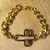 Crossed: Gold chain with a black and gold side cross.