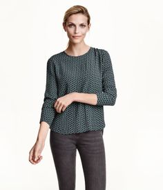 Long-sleeved blouse in a crêpe weave with buttons at the back. Slightly longer at the back.