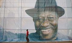 A man walks past a portrait of Nigeria's President Goodluck Jonathan