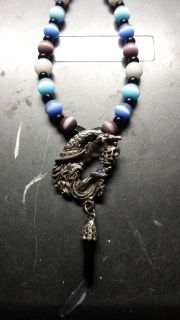 This necklace is hand beaded with black onyx, fiber-optic tiger's eye, and moonstone beads. All the beads have been chosen for their color in relation to the Eye of Mati as well as their own individual properties. The wizard charm is pewter with a small blue gem in the palm of his hand and a black pendulum hanging from the sleeve of his robe. The clasp is a pewter S hook that loops through a double jump ring and has been known to be more favored among suffers of arthritis. This necklace is…