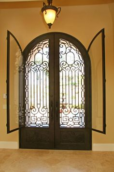 Beautiful iron and glass front doors - the windows open for cleaning and to capture a breeze...