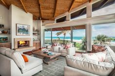 This light and airy living room boasts floor-to-ceiling windows and sliding doors that allow for waterfront views and quick access to outdoor areas. Neutral sofas and armchairs are positioned in front of a stone fireplace, while an exposed beam ceiling provides a natural finishing touch.