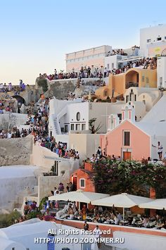Oia Santorini Greece.  Nightly gathering to watch the sunset.  When the sun finally sets below the horizon... the crowd cheers!