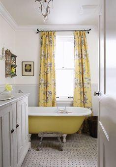 a farmhouse bathroom with yellow floral print curtains