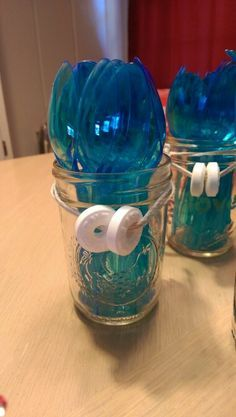 Mason jars with blue plastic ware trimmed with white life savers. Perfect for pool, ocean, surfer or shark themes.