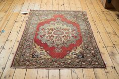 Ornate oversized medallion atop a red field in this intricate piece. Colors include grey, gold, ivory and charcoal.