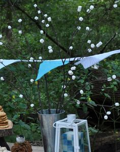 S'more camping themed birthday party.  Love the marshmallow stick centrepiece!