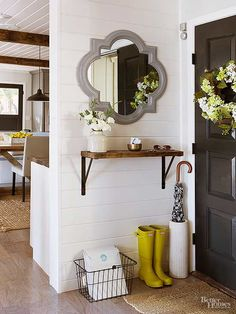 The small entryway springs to life with a few stylish touches. Dark paint updates outdated doors, while new engineered walnut flooring in a gray finish runs throughout the home for a cohesive look. A shelf made from two wood scraps (secured atop $6 brackets spray-painted black to look like iron) provides a much-needed drop zone./