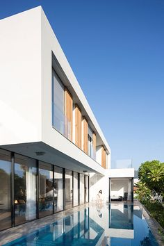"""This modern house has been designed in an """"L"""" shape that wraps around the swimming pool and has views of the park."""