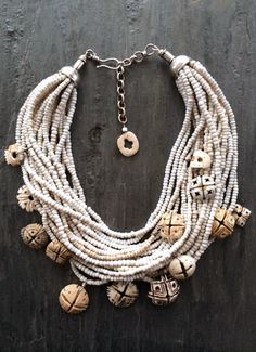 by Anna Holland | Antique carved conus shells from the deserts of Mauritania, once used as currency by tribes in Africa as early as the 14th century. With twenty strands of old white glass beads from Africa. Sterling silver cones and a hook and eye clasp | 825$