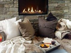 fireplace with cozy pillows and fake fur rug is a must
