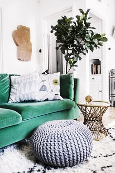 Green sofa and knitted pouf in the sitting room of the happy Swedish home of Elsa Billgren. Photography: Beata Holmgren.