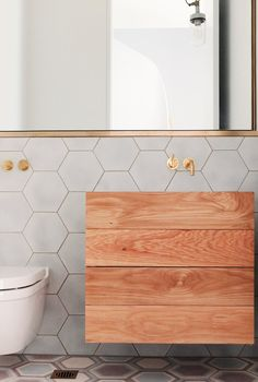 Modern free-standing wood sinkwith gold fixtures in  hexagon tiled bathroom