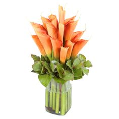 Artful on its own or anchoring an organic-chic vignette, this lovely faux calla lily arrangement showcases orange blooms in a vase with river rocks.