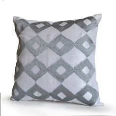 Light grey Pillows. White silk pillow with ikat embroidered in cool gray. This silk pillow looks gorgeous in white and gray. It puts a glamorous spin on a traditional pattern and it is great to mix an