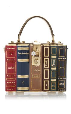 This **Dolce & Gabanna** book bag is rendered in resin and brass and features a long over the shoulder strap and lock closure.