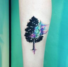 Beautiful Water Colored Tree tattoo. Another amazing tree tattoo design is next on the list. This tree is beautifully done with the play of blue, black and pink colors.
