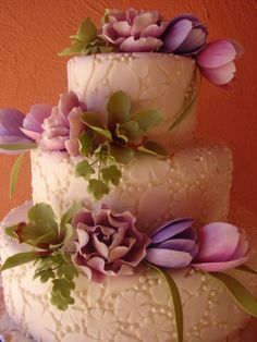 love this wedding cake. fun fondant pattern, accented by purple flowers.