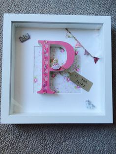 White wooden box frame with a decorative paper background and a wooden letter of your choice. Can be decorated how you would like it and can have