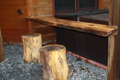 Custom wood bar top with tree trunk stools installed along the hot tub.