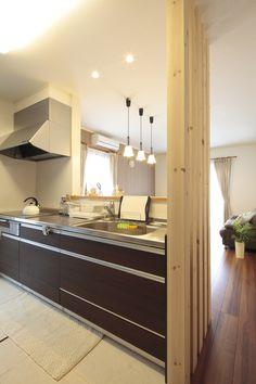 家族のつながりを重視した対面キッチンは、近くの出入り口の目隠しに杉材の化粧柱を設置。
