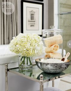 Bath essentialsA polished nickel side table with a mirrored top offers a spot to display bath essentials and a place to put down a drink or a book during a long soak.