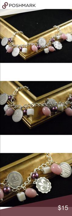 French sentiments bracelet Attached to this charm bracelet are silver plated charms that have the Fleur-de-lis, the words love, oui, Non and Amour engraved on the silver charms.  Intermingled in these charms are pink and milky white Czech glass beads and antique purple glass pearls.  This is a fun and flirty bracelet that is perfect for the spring and summer months     The bracelet measures about 7 ½ inches in length and can be adjusted. Jewelry Bracelets