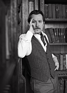 Gary Oldman in a vest and tie surrounded by books.