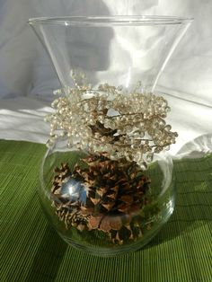 Easy Holiday Centerpiece: Pine Cones in an Hourglass Vase. Add a beaded garland or bow for extra charm!