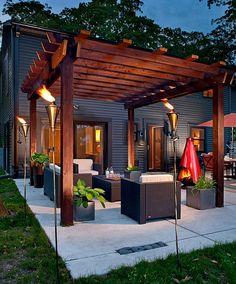 Concrete patio with pergola and tiki torches