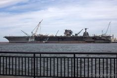 The decommissioned, deactivated aircraft carrier Enterprise (CVN-65) awaits dismantling at Newport News Shipbuilding.  The island superstructure of the new PCU Gerald R. Ford (CVN-78) can be seen in the background, astern.