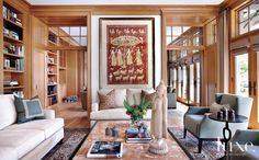 Streamlined furnishings in the living room, such as a custom sofa and loveseat designed by Jamesthomas and a Christian Liaigre armchair, are paired with more ethnic pieces like the onyx-and-wood coffee table from Bradley Hughes and a Persian carpet from Oscar Isberian Rugs.