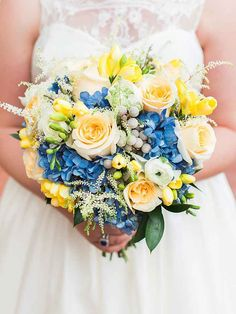 Blue and yellow wedding bouquet with ranunculus, roses, hydrangea, brunia berries and astilbes