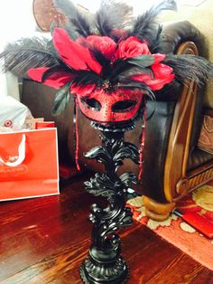 Moulin Rouge/ Masquerade party decor. Found a tall candle holder which was green ( spray painted black). Attach a styrofoam ball and hot glue rose buds, feathers, and a mask in your party colors.