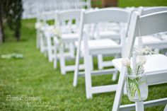 Simple glass jars wrapped with twine and filled with white flowers suspended from white americana chairs to create the aisle.