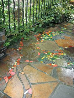 A whimsical grapevine, with colorful tile leaves and cullet glass clusters of grapes, on a stone porch built by Jim DuBois