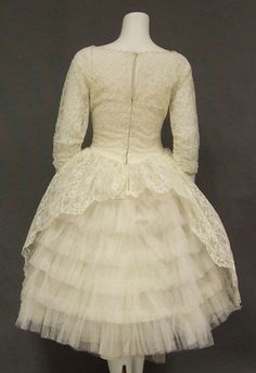 1960s Wedding Dress in ivory lace and tulle. Fitted bodice with basque waist, sheer yoke, and three quarter length sleeves.  Lace overlay is gathered into a self fabric rosette at the center front and at the rear is shorter to expose the fabulous tiered tulle underneath. (Back)