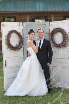 Bride and groom are in front of another lovely backdrop using vintage doors and grapevine wreaths- so shabby chic! www.facebook.com/cabincreekantiques . Photo by www.lizphotography.com