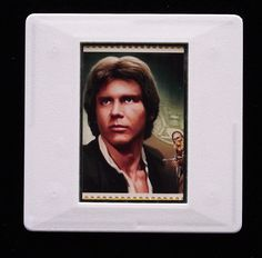 The Royal Mail released a set of special stamps featuring some of the characters, favourite droids, aliens and creatures of the Star Wars films. This 1st class stamp design shows Han Solo. Han is the captain of the Millennium Falcon. He was played by Harrison Ford in the original Star Wars trilogy. This unique and handmade brooch is an eye-catching piece, ideal to wear at any Comic Con. The unused stamp is encased in a vintage slide mount, with glass, making this a unique piece of jewellery. Star Wars Han Solo, Star Wars Film, Han Solo 2018, True Colors, Colours, Presentation Cards, Harrison Ford, Millennium Falcon, Brooches Handmade