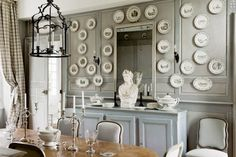 BOXWOOD TERRACE: A Designer's French Chateau - A larger collection of plates dominates another wall.  On the left, you can see the gray checked drapes at the window.
