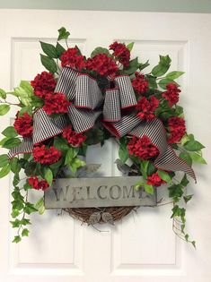 Add color to your door or porch with this red geranium welcome door wreath. This decorated grapevine wreath is made using red geraniums and mixed greenery with a black and white check bow to accent the flowers. I add a metal welcome sign that has a sweet little bird sitting on