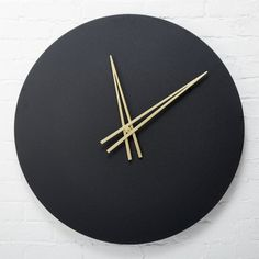 Shop Ora Black Wall Clock. Minimalist black wall clock keeps count sans numbers. Brushed brass-coated hands punctuate black round iron with sleek form.