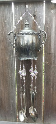 "Anitque Silver Plate Pot Up-cycled Into A Chime. This stunningly unique chime was made from an antique silver plated pot/sugar bowl. This chime is ""one of a kind"" and would look great on a patio, fence, porch or the kitchen window. It is incredibly detailed with gorgeous flowers and designs. There are 6 antique silver plated spoons hanging. Antique silverware has a brass base which creates the most peaceful sound in a light breeze! The hand-crafted lampwork beads were carefully picked to…"
