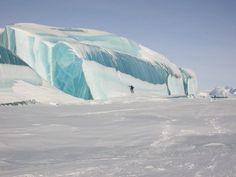 Rolling blue waves hit the Antarctic coastline
