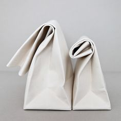   WHITE   This white minimalist leather clutch is folded from a single piece of leather and comes with a brass snap closure.