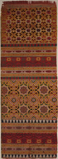 """14th century; Nasrid Spain   This silk textile fragment displays two scripts. The knotted kufic inscription woven in black repeats the word beatitude and runs on a wide red-ground border. The decorative calligraphy is in harmony with the geometric design of the fabric. The naskhi script, which reads, """"good luck and prosperity,"""" is less easily discernible, filling the small cartouches outlined in white lines within the narrower border. Metropolitan Museum of Art"""