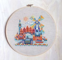 This modern cross stitch pattern of Amsterdam features the Royal Palace of Amsterdam, the Rijksmuseum, the Amsterdam Centraal Railway Station, the